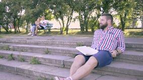 Kopplar av den läs- tidningen för den unga mannen, sammanträde på trappa arkivfilmer
