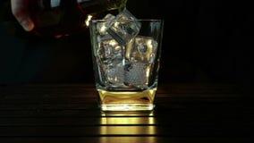 Kopplar av hällande whisky för bartendern i exponeringsglaset med iskuber på den wood tabellen och mörk bakgrund för svart, fokus lager videofilmer