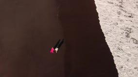 kopplar ihop den flyg- videoen för den bästa sikten för flyget 4K av barn på stranden med svart vulkanisk sand på solnedgångtid B arkivfilmer