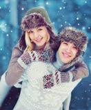 Kopplar ihop det lyckliga le barnet för stående i vinterdagen som har gyckel, mannen som på ryggen ger ritt till kvinnan över snö Arkivbild