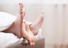 Kopplar ihop fot i säng. Arkivbilder