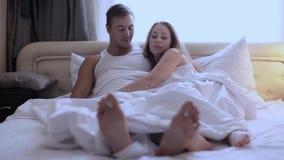 Kopplar ihop fot som ut från under klibbar duntäcket hemma i sovrum lager videofilmer