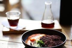 Kopplar ihop sunda svarta riskotletter för strikt vegetarian som tjänas som med orange morötter, och microgreeens och decafkaffe  royaltyfri fotografi