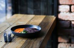 Kopplar ihop sunda svarta riskotletter för strikt vegetarian som tjänas som med orange morötter, och microgreeens och decafkaffe  arkivfoton