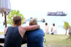 Kopplar ihop turister som tycker om havsikter på stranden royaltyfri bild