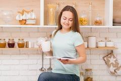 Kopplat av hem- te för fritidkvinnadrinken läste kök arkivbilder