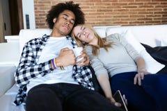 Kopplat av ungt par som har stupat sovande, medan hålla ögonen på TV på soffan hemma royaltyfria foton