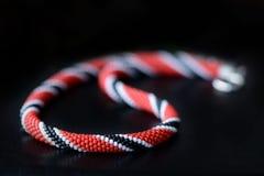 Koralik kolii szydełkowa czerwień, czarny i biały kolory na ciemnym tle royalty ilustracja