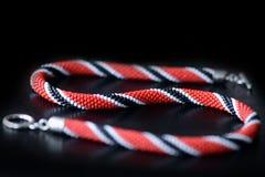 Koralik kolii szydełkowa czerwień, czarny i biały kolory na ciemnym tle ilustracja wektor