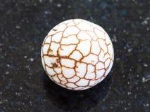 Koralik od krakingowego Cacholong gemstone na zmroku Obrazy Stock