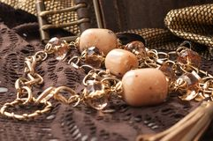 koraliki i złoty łańcuch blisko rzemiennego paska na brązie textured koronkę zdjęcia stock