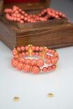 Korall prytt med pärlor armband arkivfoto