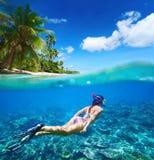 Korallenriff im tropischen Meer auf einem Hintergrund von grüner Insel Stockbild