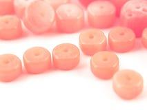 Korallenrote Perlen des natürlichen Edelsteinrosas auf einem weißen Hintergrund Lizenzfreie Stockfotos