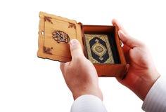 Koran, asimiento del libro sagrado del Islam por las manos masculinas foto de archivo libre de regalías