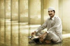 Koran de leitura dos povos muçulmanos asiáticos novos Fotografia de Stock Royalty Free