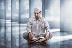 Koran de leitura dos povos muçulmanos asiáticos novos Foto de Stock Royalty Free