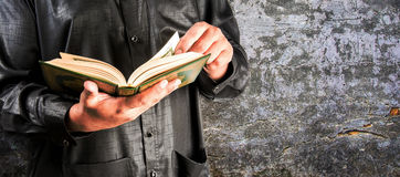 Koran in hand - holy book of Muslims. Public item of all muslims Stock Image