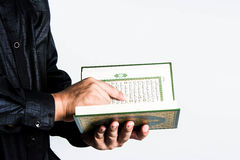 Koran in hand ,Quran in hand  - holy book of Muslims , on white background Royalty Free Stock Photo