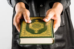 Koran in hand ,Quran in hand  - holy book of Muslims , on white background.  Royalty Free Stock Photos