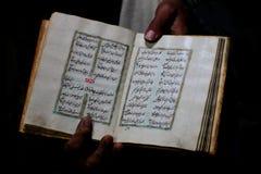 Koran, holly book of Muslims. Ancient book of Koran held in hands Royalty Free Stock Photos
