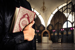 Koran with muslims man . Mosque background . Koran - holy book of Muslims.  Royalty Free Stock Photography