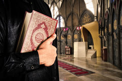 Koran with muslims man . Mosque background . Koran - holy book of Muslims.  Royalty Free Stock Photo