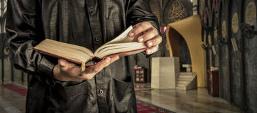 Koran with muslims man . Mosque background . Koran - holy book of Muslims.  Royalty Free Stock Photos