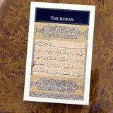 Koran paperback square. The revelations of Muhammad Islamic Koran pocket paperback book unopened on brown table for ease of carrying in pocket and the koran royalty free stock images