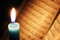 Koran or quran holy book with candle on candlelight. Opened koran or quran, holy book of Islam religion with  candlelight Royalty Free Stock Images