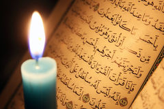 Koran or quran holy book with candle on candlelight. Opened koran or quran, holy book of Islam religion with  candlelight Stock Photo