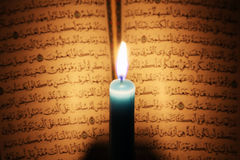 Koran or quran holy book with candle on candlelight. Opened koran or quran, holy book of Islam religion with  candlelight Stock Photos