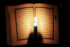 Koran or quran holy book with candle on candlelight. Opened koran or quran, holy book of Islam religion with  candlelight Royalty Free Stock Image