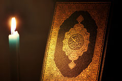 Koran or quran holy book with candle. Closed koran or quran, holy book of Islam religion with  Candle Stock Image