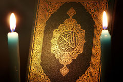 Koran or quran holy book with candle. Closed koran or quran, holy book of Islam religion with  Candles Stock Image