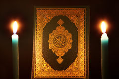 Koran or quran holy book with candle. Closed koran or quran, holy book of Islam religion with  Candles Stock Photography