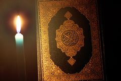 Koran or quran holy book with candle. Closed koran or quran, holy book of Islam religion with  Candles Stock Images