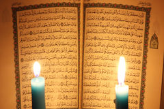 Koran or quran holy book with candles. Opened koran or quran, holy book of Islam religion with  candlelight Royalty Free Stock Photography