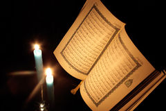 Koran or quran holy book with candles. Opened koran or quran, holy book of Islam religion with  candlelight Stock Images