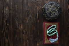 Koran with rosary beads and pray hat on wooden background. Islamic concept with copy space. Quran with rosary on wooden background royalty free stock photos