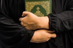 Koranen i handen - helig bok av Koranen för muselmaner (offentliga muslims för objekt allra) i handmuslimskvinna arkivbilder