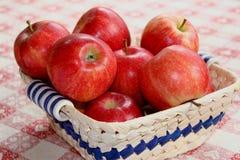 Korb der Äpfel auf rotem u. weißem Tuch Stockbild