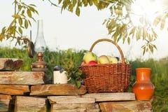 Korb des Apfels mit alter Lampe und Becher Pflaumen Stockfotografie