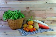 Korb des Gemüses auf dem hölzernen Hintergrund Stockfotografie