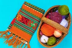 Korb mit Bällen der Wolle und der Stricknadeln auf einem blauen Hintergrund stockbild