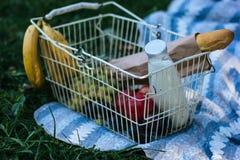 Korb mit Bananen, Trauben, Äpfeln, Stangenbrot und Flasche Milch stockfotos