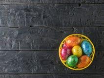 Korb mit bunten Eiern auf einer schwarzen rustikalen Tabelle Die Ansicht von der Oberseite Stockbilder