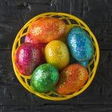 Korb mit bunten Eiern auf einer schwarzen Tabelle Die Ansicht von der Oberseite Lizenzfreie Stockbilder