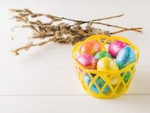 Korb mit bunten Eiern auf einer weißen rustikalen Tabelle Lizenzfreie Stockfotografie