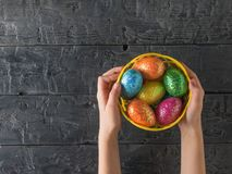 Korb mit bunten Eiern in den Händen eines Kindes auf einer rustikalen Tabelle Stockfotografie
